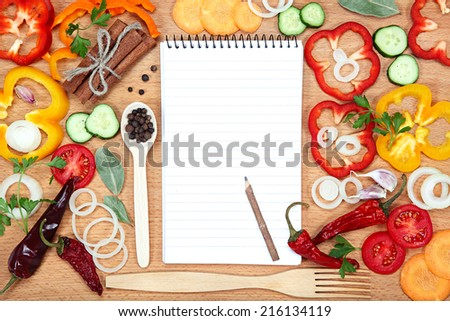 Vegetables, spices and notepad for recipes, on wooden table. #216134119