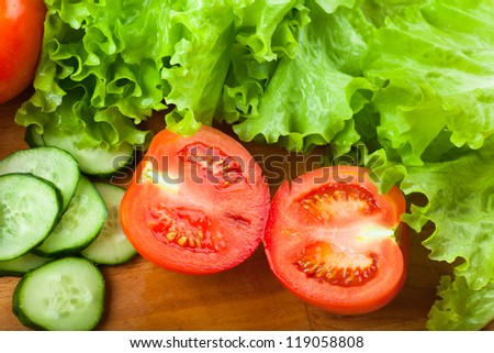 Vegetables (tomato, cucumber, salad) on a wooden table