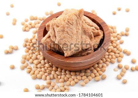 Vegetarian alternative to meat and vegan food option concept with photograph of soya textured chunks in wooden bowl and soy beans isolated on white background