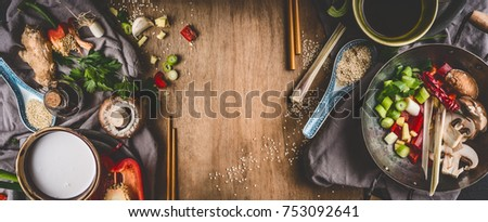 Vegetarian Asian cuisine ingredients for stir fry with chopped vegetables, coco milk, spices,chopsticks and wok pot on rustic wooden background, top view, banner. Chinese or Thai food cooking