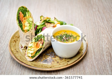 vegetarian avocado tortilla wrap sandwich and cup of decorated soup on rustic plate