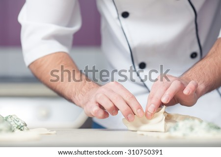Vegetarian bakery concept. Chef cook in uniform putting filler of spinach and soft feta cheese on slice of puff pastry and making french chausson. Close up. Indoor shot