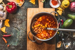 Vegetarian Bean soup in cooking pot with ladle on wooden cutting board with ingredients on dark rustic background, top view, frame. Mexican cuisine
