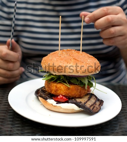 Vegetarian Burger containing deep-fried Camembert in Panko breadcrumbs, grilled Aubergine, Sour Cream, Sun-dried Tomatoes, Salad and Onions.