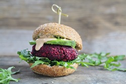 Vegetarian burger made of beetroot, broccoli and chickpeas with avocado and arugula