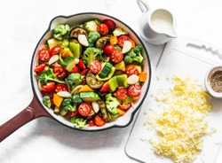 Vegetarian casserole ratatouille, baked in a frying pan on a light background, top view