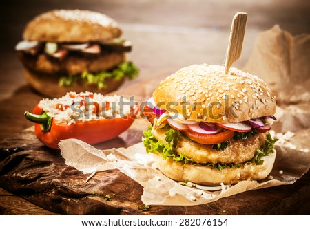Vegetarian Couscous Burgers with Fresh Toppings and Sesame Seed Roll Accompanied by Stuffed Pepper on Brown Paper Wrapper