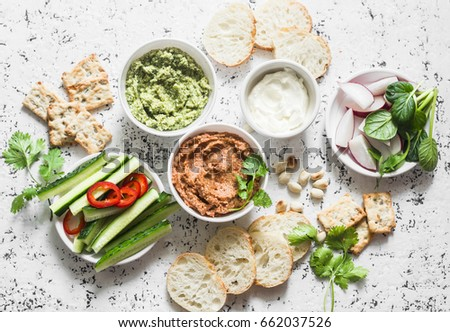 Vegetarian dip table. Eggplant, harissa, walnuts dip, broccoli dip, soft tofu and fresh vegetables on a light background, top view. Flat lay      #662037526