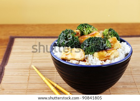 Vegetarian dish of stir fried tofu, broccoli and orange sauce with chopsticks. Selective focus with shallow depth of field.