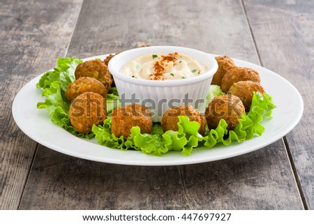 Vegetarian falafels and hummus on a rustic wooden table