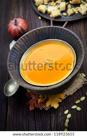 Vegetarian food concept. Pumpkin soup with pumpkin seeds, croutons and garnish on wooden background. Thanksgiving dinner