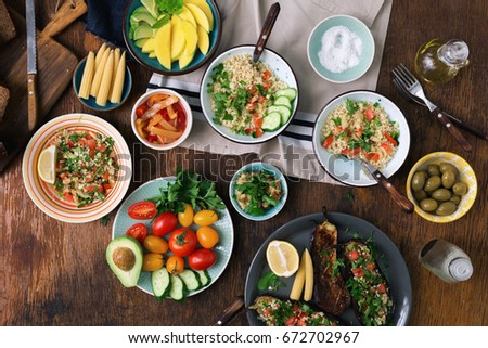 Photo of  Vegetarian food concept. Set of healthy vegetarian food, salad with bulgur porridge and vegetables, stuffed eggplant, vegetables, mango, avocado and snacks on a wooden table, top view