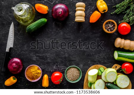 Vegetarian food concept. Set of vegetables for stew. Squash, bell pepper, tomato, spices, oil on black background top view space for text #1173538606