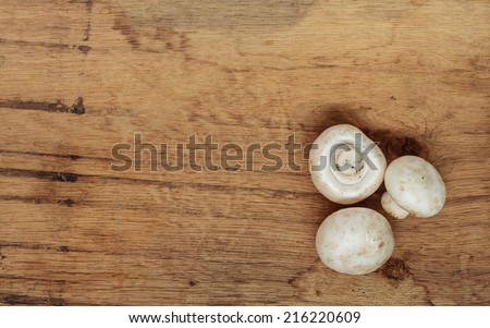 Vegetarian food. Fresh white mushrooms champigonons on wooden kitchen table as background.