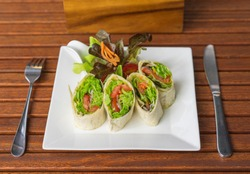Vegetarian food. Organic vegetables roll with green salad on a plate with fork and spoon. Wooden table, close up