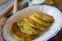 Vegetarian food. Zucchini fritters, thin pancakes and sauce on white plate over wooden table. Squash pancakes