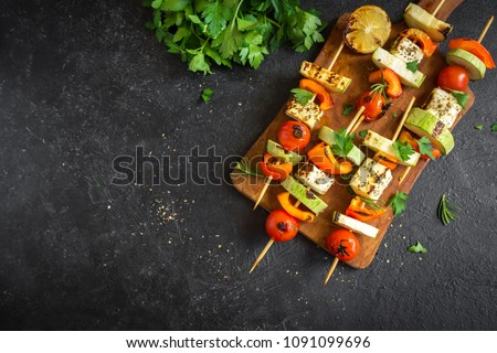Vegetarian grilling. Vegetarian skewers with halloumi cheese and vegetables on black background, copy space.