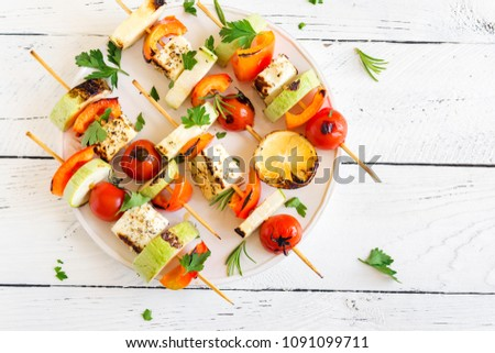 Vegetarian grilling. Vegetarian skewers with halloumi cheese and vegetables on white background, copy space.