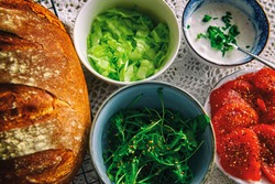 Vegetarian healthy breakfast containing homemade bread, vegetables tomatoes, argula with sesame seed, sald, iceberg lettuce and garlic sauce with chives