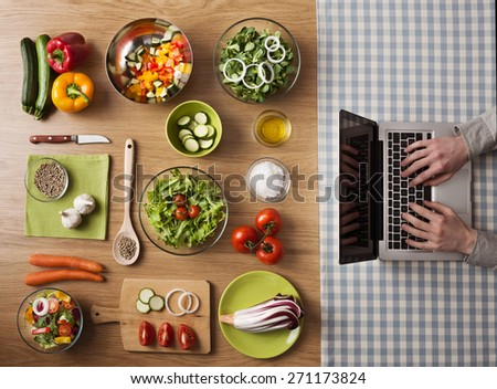 Vegetarian healthy food preparation at home on kitchen table with hands typing on a laptop on the right, top view
