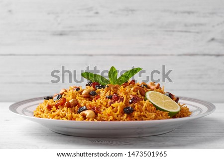 Vegetarian Kabsa known as Biryani or Danbauk. Ramadan food. Kabsa is traditional saudi arabian cuisine dish. Kabsa cooks with basmati rice, spices, tomatoes, nuts and raisins. Copy space