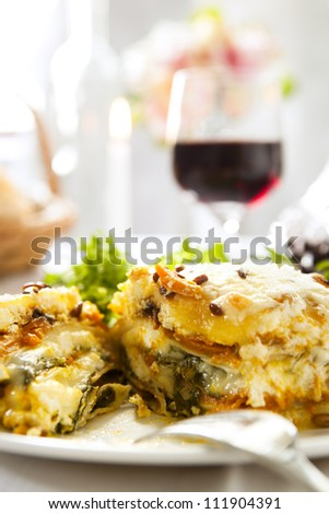 Vegetarian lasagne with salad and a glass of red wine.