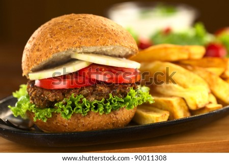 Vegetarian lentil burger in wholewheat bun with lettuce, tomato and cucumber accompanied by French fries (Selective Focus, Focus on the front of the sandwich)