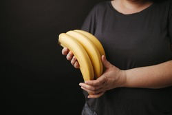 Vegetarian lifestyle, conscious eating, nutrition choices, mindfulness and healthy food. Woman holding bananas in hands