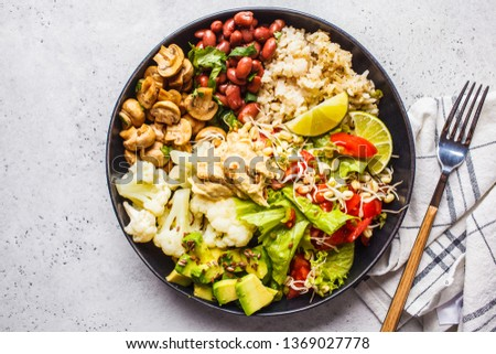 Vegetarian lunch. Brown rice with mushrooms, beans, salad and hummus in a black plate, clean eatind, top view.