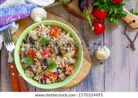 Vegetarian menu, healthy diet food. Rice with vegetables, mushrooms and eggplants in a bowl on a wooden table. Top view on a flat lay.