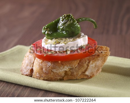 Vegetarian �montadito� with tomato, goat cheese and pepper. Montadito is an appetizer or snack (Spanish Tapa) made with a slice of bread with some other food on it.