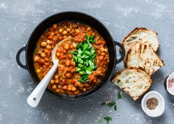 Vegetarian mushrooms chickpea stew in a iron pan and rustic grilled bread on a gray background, top view. Healthy vegetarian food concept. Vegetarian chili