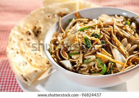 Vegetarian noodles and butter naan on the table in restaurant in Varkala, Kerala, India