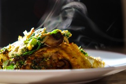 Vegetarian omelette with broccoli, spinach and mushrooms. Steaming hot plate of food. Healthy and nutritious meal or a pre workout or post workout snack. Nutritious and fresh food.