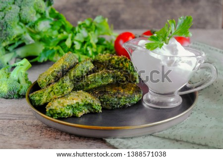 Vegetarian patties on a plate with the tomatoes. Served with sour cream sauce. Healthy vegetarian or vegan food.Lie on the cutting Board with tomato greens.  #1388571038