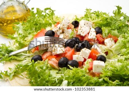 vegetarian piadina with fresh salad, tomatoes, olives and mozzarella cheese