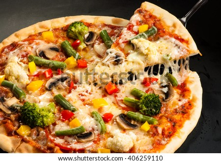 vegetarian pizza on a dark background with mushrooms, cheese and sweet pepper, cutting #406259110
