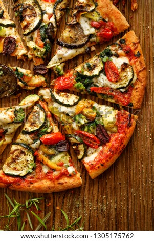 Vegetarian pizza with addition grilled vegetables and aromatic herbs, divided into portions on a wooden background, top view