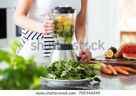 Vegetarian preparing vegan smoothie with rucola, citrus, cucumber in kitchen with carrots on countertop