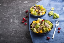 Vegetarian salad from romanesco cabbage, champignons, cranberry, avocado and pumpkin on a black concrete background and blue textile. side view, copy space.