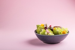 Vegetarian salad from romanesco cabbage, champignons, cranberry, avocado and pumpkin on a pastel pink background. side view, copy space.