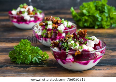 Vegetarian salad with baked beet, Greek yogurt, fresh parsley, walnuts and feta cheese in small glass bowls on the rustic wooden table.