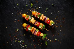 Vegetarian skewers with halloumi cheese and mixed vegetables on black background, top view