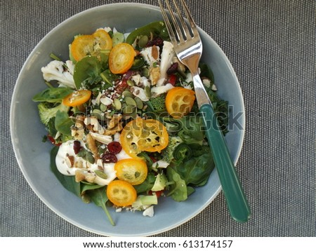 Vegetarian spinach salad with raw broccoli, cauliflower and paprika. Sprinkle from a mixture of seeds and nuts and slices of kumquat. #613174157