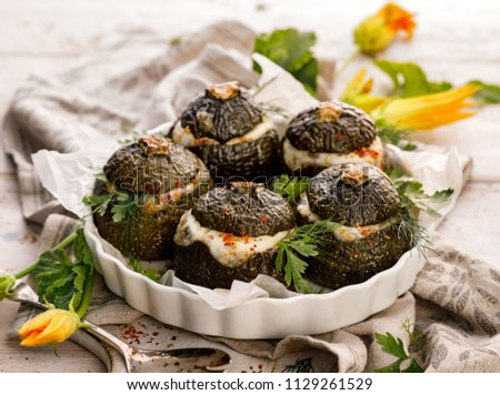Vegetarian stuffed zucchini. Baked round courgettes, stuffed with rice, mushrooms and cheese with the addition of aromatic herbs in a baking dish on a wooden white table