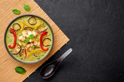 Vegetarian Thai Green Curry with tofu in black bowl at dark slate background. Veg Green Thai Curry is thailand cuisine dish with green chillies paste, basil, spices and vegetables. Copy space