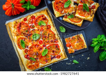 Vegetarian tomato tart or puffed pizza with herbs on black background Photo stock ©