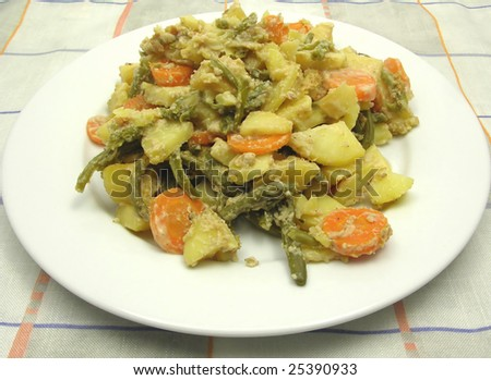 Vegetarian vegetable casserole on a white plate and checked tablecloth