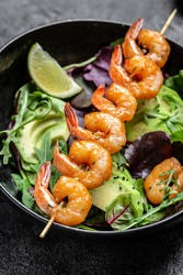 Vegetarian vegetable low carb lunch bowl with avocado, fresh salad, grilled shrimps and pesto sauce. Healthy diet seafood concept. Top view. vertical image.