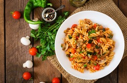 Vegetarian Vegetable pasta Fusilli  with zucchini, mushrooms and capers in white bowl on wooden table. Top view